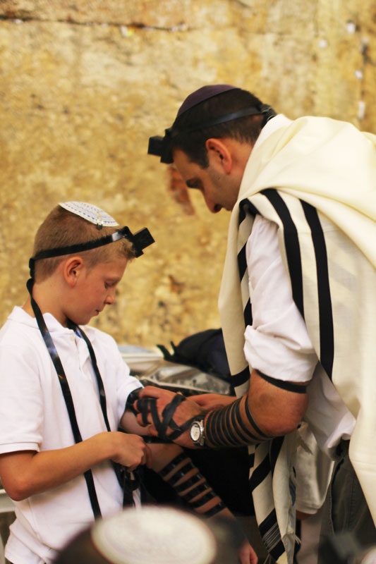A father showing his son how to wear Tefillin correctly.